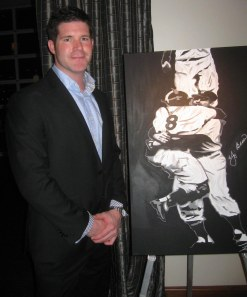 Professional baseball player turned artist Kevin Rival poses with one his prize paintings